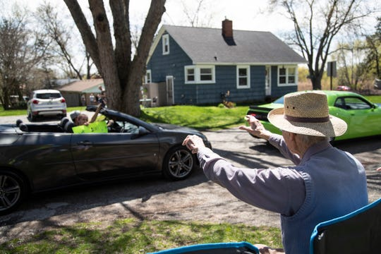 Jim Curry, right, a WW II veteran, who is turning 100 on Monday, waves at his granddaughter Ashley Curry, as she drives by his home in Commerce Township to wish him happy birthday, Sunday, May 3, 2020.