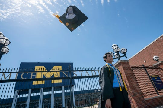 University of Michigan Biology major Noah Nugent, of Bath, Michigan, throws his cap into the air as he poses for photos at Michigan Stadium in Ann Arbor, May 3, 2020. On what was supposed to be weekend of graduation commencement, students were unable to walk across the stage due to COVID-19 canceling all public events.