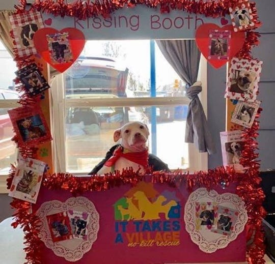 Kisska poses in a kissing booth.