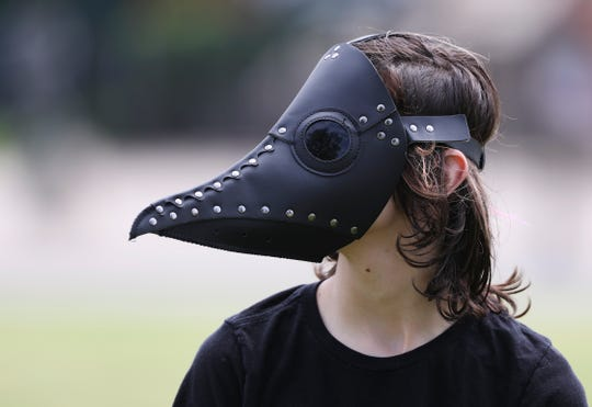 James Milburn, 14, wears a costume plague doctor mask as he and his family visit Waterfront Park on Sunday.