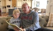 """Chris Mack reads the book """"Mama's Right Here"""" to his son, Brayden."""