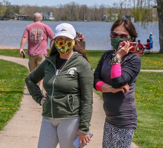 Ruby Wicker, left, and Grace Firek take a walk near Lake Lansing on Sunday, May 3, 2020. They both wondered why so many people were not wearing masks.
