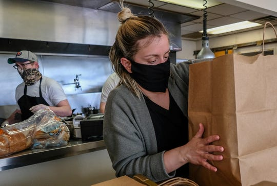 Taylor Kennedy, a server/bartender at Red Haven  Farm to Table Restaurant in Okemos, packs-up an order for a customer to be picked up Saturday, May 2, 2020.