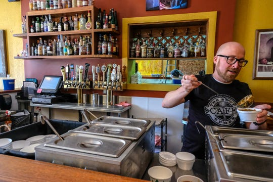 Keith Buchele, General Manager at The Soup Spoon Cafe in Lansing prepares several bowls of soup for a take-out order Saturday, May 2, 2020.
