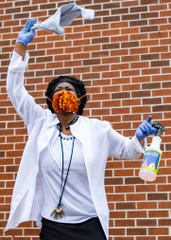 Shirley Seff dances with cleaning spray and a towel in hand during a drive-in worship service in a parking lot at Pentecostal Temple Church of God in Christ in Memphis, Tenn., on Sunday, May 3, 2020.