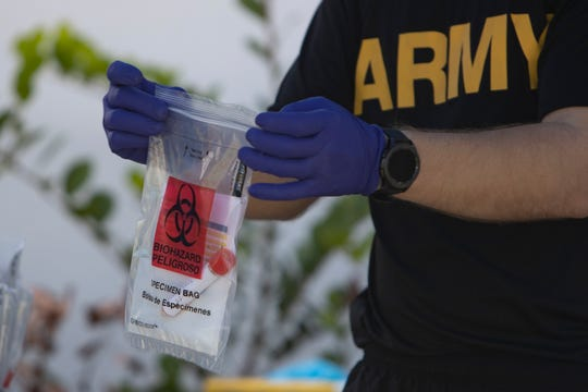 A Florida National Guardsman collects samples, Sunday, May, 3, 2020, at a COVID-19 test site at the Collier County Health Department in Immokalee.