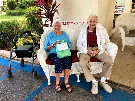 Yolanda and Joe Tenaglio sit in front of their home at the Lely Palm senior residential community before being honored by a 20-car parade in celebration of the couple's 73rd wedding anniversary Sunday, May 3, 2020.