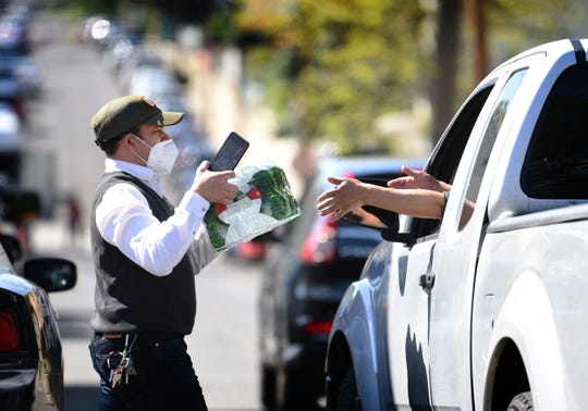 Mildred Casado Mayor's assistant, hands a pack of water bottles to a driver as the City of Passaic is giving out cases of bottled water to its residents at Dignity House in Passaic on 05/03/20.