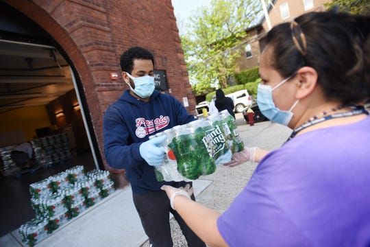 Batner Bonifacio (L), who works at Passaic Recreation) hands a pack of water bottles to a resident as the City of Passaic is giving out cases of bottled water to its residents at Dignity House in Passaic on 05/03/20.