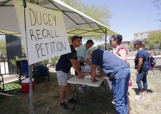 People sign a petition to recall Arizona Gov. Doug Ducey during a rally to open the state at Wesley Bolin Plaza in Phoenix on May 3, 2020.