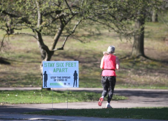 Signs have been placed around Highland Park in Rochester reminding visitors to stay six feet apart. On Friday, Gov. Andrew Cuomo signed an executive order allowing gatherings of up to 10 people.