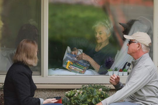 Judie Shape, center, who has tested positive for the new coronavirus, but isn't showing symptoms, opens a care package of art supplies from her daughter Lori Spencer, left, and her son-in-law Michael Spencer, Tuesday, March 17, 2020, as they talk on the phone and look at each other through a window at the Life Care Center in Kirkland, Wash., near Seattle. In-person visits are not allowed at the nursing home, which is at the center of the outbreak of the new coronavirus in the United States. (AP Photo/Ted S. Warren)