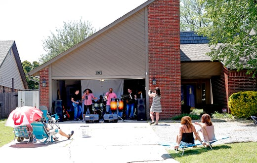 The band Hypnotik performs out of a garage in a Northwest Oklahoma City neighborhood, for a social distance concert for neighbors, Saturday, May 2, 2020.