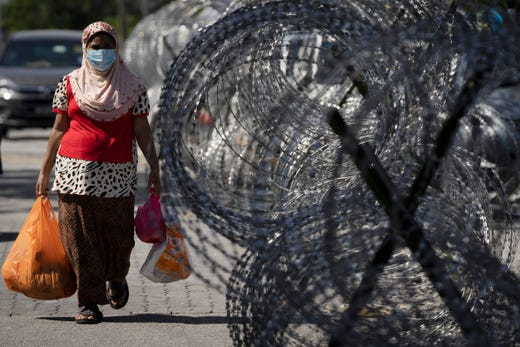 A woman walks home with groceries next to barbed wire in the coronavirus locked down area of Selayang Baru, in Kuala Lumpur, Malaysia, on Sunday, May 3, 2020. The Malaysian Prime Minister Muhyiddin Yassin says the economy needs to be revived as billions have been lost during the partial lockdown that began in March.