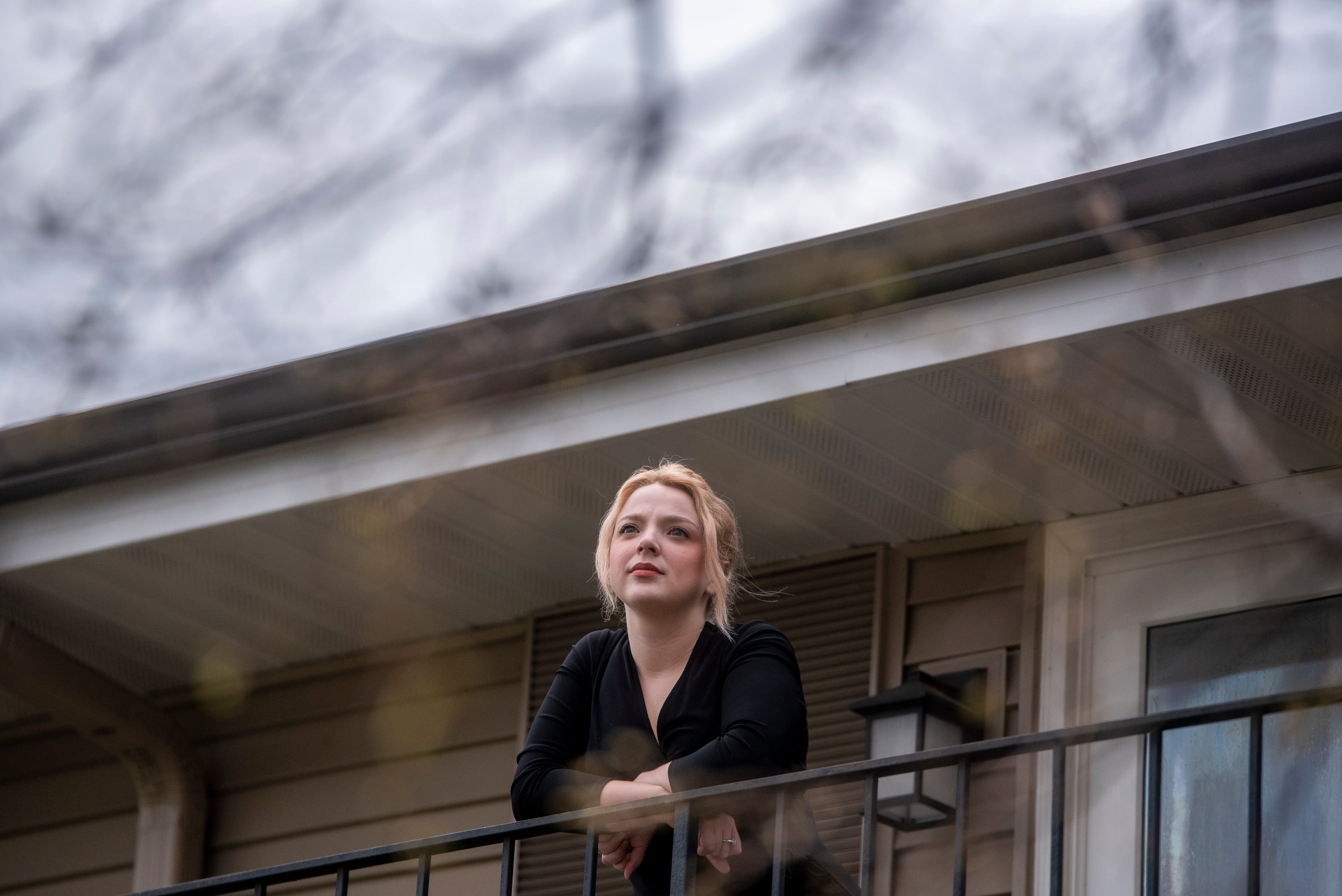 Rachel Metcalfe, 22, poses on her balcony in Naperville, Illinois, on Friday, May 1, 2020. Metcalfe went from having a full-time job and living comfortably to applying for unemployment and wondering how she was going to pay rent as she recovered from COVID-19.