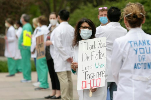Dozens donned masks along with scrubs and white coats as the Physicians Action Network held a public rally in support of Dr. Amy Acton at the Ohio Statehouse in downtown Columbus on Sunday, May 3, 2020. Doctors stood six feet apart, marked by lengths of rope, to highlight the value of social distancing during the COVID19 pandemic. The rally was a response to protestors of the state's Stay at Home orders who demonstrated outside Acton's home in Bexley on Saturday.