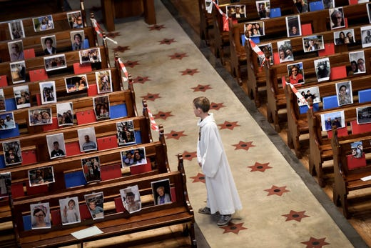 An altar boy stands in the central aisle of the Basilica of Neuchatel which pews display the portraits of 400 parishioners unable to attend the mass due to the COVID-19 outbreak,  caused by the novel coronavirus, on May 3, 2020.  Switzerland started to ease the restrictions imposed to control the COVID-19 pandemic but masses are still forbidden.