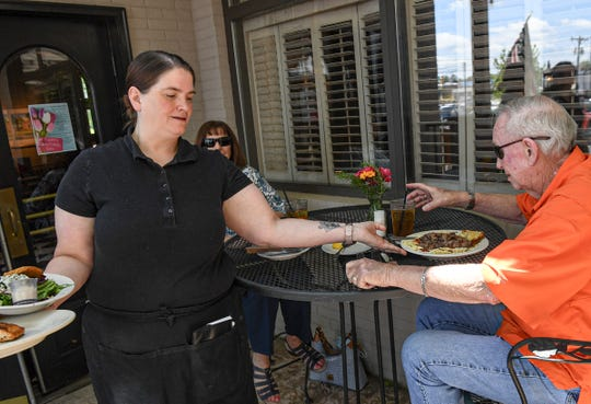 Laura Williams, left, manager of Tucker's restaurant, serves Kathy O'Connor and Tom O'Connor of Anderson in Anderson, S.C. Monday, May 4, 2020. State Gov. Henry McMaster announced May 1 that restaurants could reopen outdoor dining spaces May 4, as long as they follow standards on cleaning and social distancing. Since March 18, restaurants have been restricted to curbside or delivery services in response to concern for public health during the coronavirus pandemic.