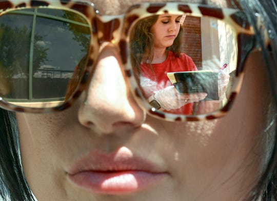 Server Morgan Veane, seen in the reflection of sunglasses, takes an order from Terri Smith of Starr outside at Raines on Main in downtown Anderson, S.C. Monday, May 4, 2020. State Gov. Henry McMaster announced May 1 that restaurants could reopen outdoor dining spaces May 4, as long as they follow standards on cleaning and social distancing. Since March 18, restaurants have been restricted to curbside or delivery services in response to concern for public health during the coronavirus pandemic.