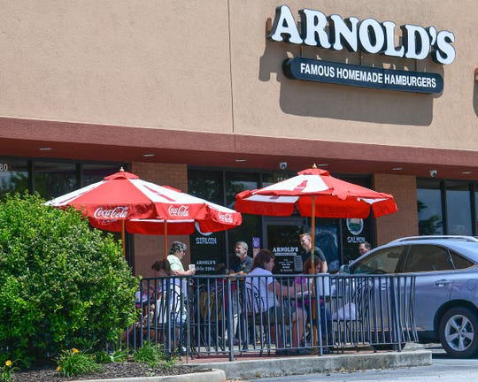 People eat outside at Arnold's Famous Homemade Hamburgers in Anderson, S.C. Monday, May 4, 2020. State Gov. Henry McMaster announced May 1 that restaurants could reopen outdoor dining spaces May 4, as long as they follow standards on cleaning and social distancing. Since March 18, restaurants have been restricted to curbside or delivery services in response to concern for public health during the coronavirus pandemic.