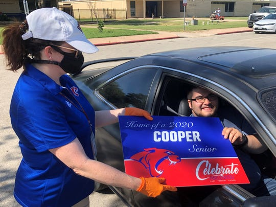 Devin Hernandez, 18, right, collects a yard sign recognizing graduating seniors from Cooper High School teacher Sherry Griffith Monday. The signs were distributed to seniors at all three Abilene ISD high schools Monday, recognizing them for their accomplishments during a pandemic that has forced many senior activities to either cancel or be postponed.