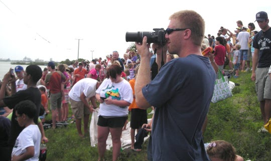 Crowds along the Beachline watch the launch of the shuttle Atlantis. Chris Mabry from Austin TX photographs the last shuttle launch.