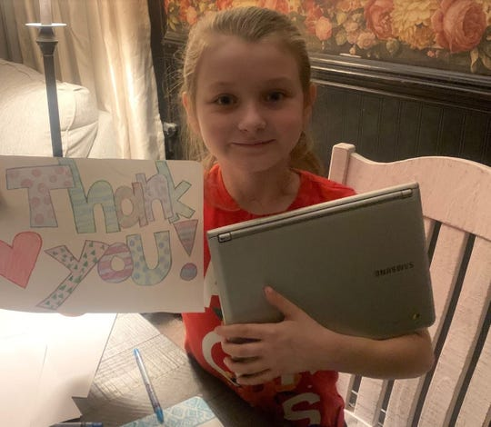 Katrina McClatchey, a Sayler Park School 4th grader poses with her school laptop.