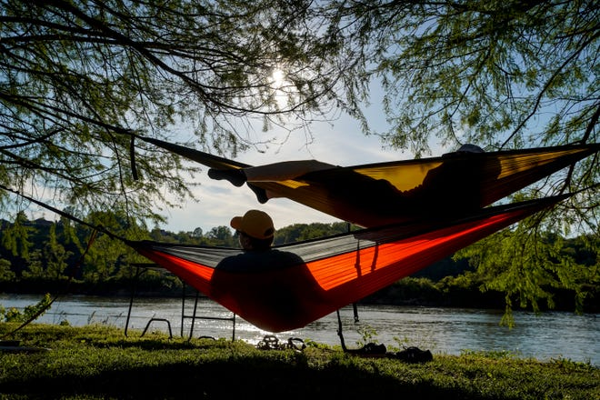Jacob Hardy, bottom, and Eric Rittenberry, top, hang in hammocks on their first gathering out after safer at home orders expired at Liberty Park in Clarksville, Tenn., on Friday, May 1, 2020.