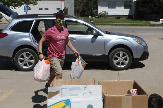Volunteer Nicholas Koenig unloads a box of food picked up from a donor's home. The Feed It Forward Indianola movement collected donations for the Helping Hand and other area food banks on May 3. Volunteers picked up food at addresses throughout the Indianola and also accepted donations at Grace Evangelical Free Church.