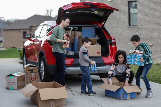 Tony and Evita Vittorini, both 37, of Rochester Hills have started a Food 4 Families website to raise money to buy food for a local food bank, Neighborhood House. The Vittorinis with help from their sons Valentino, 8, and Cristiano, 6, pack boxes of food to take to the food pantry.
