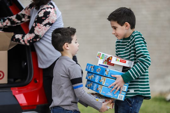 Cristiano, 6, and Valentino Vittorini, 8, pack food into boxes to take to a local food pantry, Neighborhood house, with their parents, Tony and Evita Vittorini at their home in Rochester Hills, Mich., on Saturday, May 2, 2020.