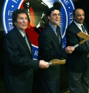 Red Wings owner Mike Ilitch, Pat LaFontaine and Grant Fuhr  were all inducted into the Hockey Hall of Fame in Toronto on Monday, Nov. 3, 2003. After being presented with their Hall of Fame blazers and rings they gathered around the hall emblem for photos and flipped hockey pucks into the air.