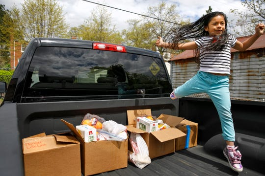 Allison, 5, leaps over four boxes of food that her parents have painstakingly gathered from food banks and churches, over the course of two weeks, to bring to her aunts and cousins in Baltimore who are having trouble finding enough food to eat, Tuesday, April 14, 2020, in Washington.