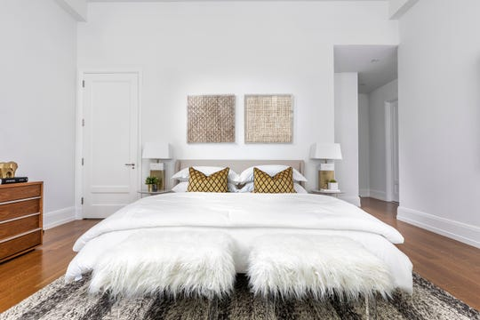 Faux fur stools with acrylic legs add a touch of glamour to this bedroom.