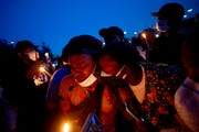 Maalik Mitchell, center left, sheds tears as he says goodbye to his father, Calvin Munerlyn, during a vigil Sunday, May 3, 2020, in Flint, Mich. Calvin Munerlyn was shot and killed after denying a maskless woman entry to the Family Dollar store he worked at in Flint.