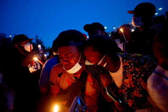Maalik Mitchell, center left, sheds tears as he says goodbye to his father, Calvin Munerlyn, during a vigil Sunday, May 3, 2020, in Flint, Mich.