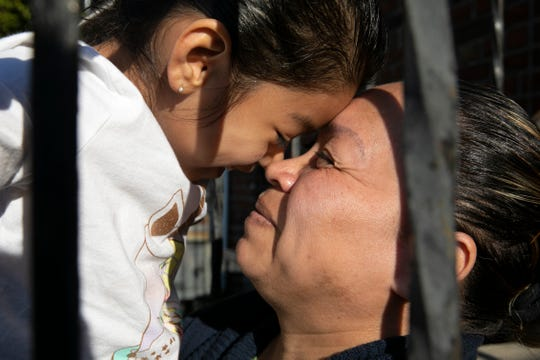 Allison, 5, rubs noses with her mother, Janeth, on the back steps of their building, Wednesday, April 15, 2020, in Washington.