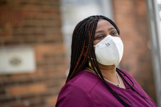 Marsha Jenkins, an environmental house keeper for Lakepointe Senior Care and Rehab Center in Clinton Township, poses for a photo in front of her home in Detroit, May 3, 2020.
