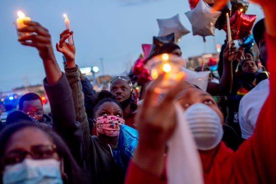 Family and friends lift their candles to the sky and release balloons to honor Calvin Munerlyn during a vigil Sunday, May 3, 2020, in Flint, Mich.