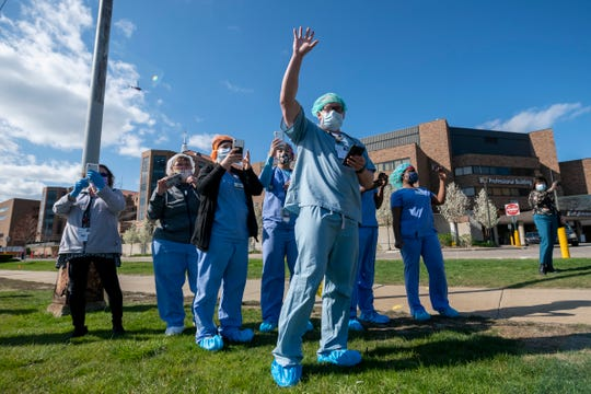 Workers with Ascension St. John Hospital, watch, wave, and take photos as a parade of first responders and health care workers moving past Ascension St. John Hospital, in Detroit, May 4, 2020. Multiple police and fire departments participated in the parade to honor the workers dealing with treating COVID-19 patients.
