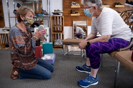 Janie Antes, left, shows Sara Burk of Evansville's West Side a pair of sandals at Thomas's Shoes at 2227 W. Franklin Street Monday afternoon, May 4, 2020. It was the first day the business had been fully open since the start of the COVID-19 pandemic.