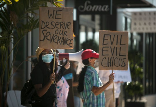 """Damisa Cooper, left, and Cheryl Welton, right, were out protesting Chico's on Monday, May 4, 2020, in south Fort Myers. Cooper, Welton and many other Chico's employees were laid off without severance pay after being furloughed or working for reduced pay due to the COVID-19 pandemic. """"It's very upsetting the way they're treating everyone,"""" Cooper said. Cooper worked for the company for two years after graduating from FGCU."""