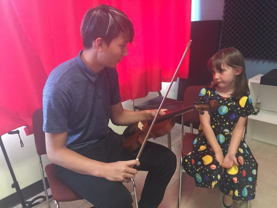 Teacher Travis Phan shows Piper Golio, 6, some fundamentals of playing the violin at D Guitars and Lutherie in early March.