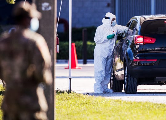 Members of the National Guard takes samples from people getting tested for COVID-19 at Century Link Sports Complex in Fort Myers on Monday, May 4, 2020. A COVID-19 drive in testing site has been set up by the National Guard. Collections will start at 9 a.m. and last until 5 p.m for an indefinite period of time.