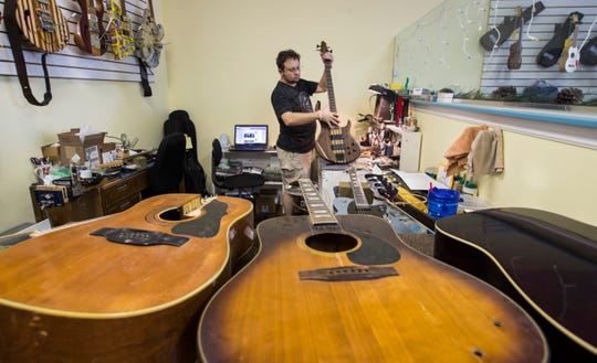 Doron Markowitz works on a bass guitar tune-up at his shop.