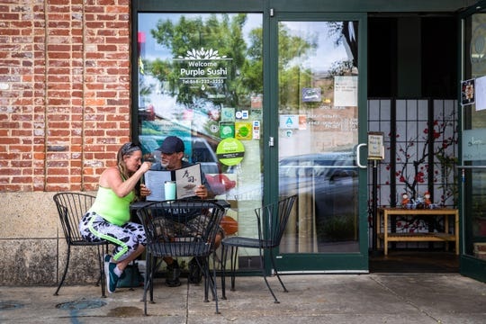Lilly Parks and Eddie Connolly decide on their orders at Purple International Bistro and Sushi on Main Street in Greenville, Monday, May 4, 2020, the first day that restaurants downtown began to reopen outdoor seating since Governor Henry McMaster banned on-premises dining on March 18.