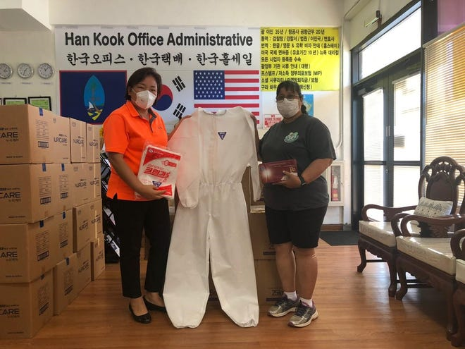 Ina Lee, owner of Han Kook Wholesale in Barrigada, and Dededo Mayor Melissa Savares, show $5,000 worth of personal protective equipment donated by the company to the Mayors' Council of Guam.