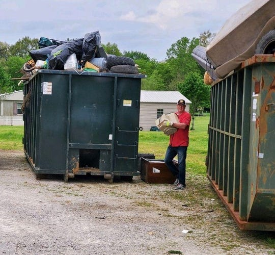 Henderson County Judge Executive Brad Schneider cleans up around dumpsters at Smith Mills Volunteer Fire Department after people filled dumpsters and left trash on the ground (May 2020).
