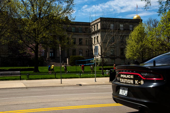 A University of Iowa police car drives along Clinton Street as a group plays volleyball on the Pentacrest during the novel coronavirus pandemic, Sunday, May 3, 2020, on the University of Iowa campus in Iowa City, Iowa.