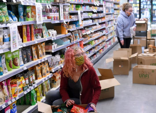 GreenStar Food Coop employees stock shelves on Monday, May 4, 2020, in preparation for the May 6 morning opening of the new Cascadilla Street location.